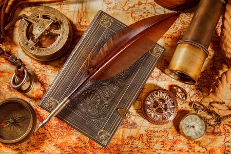 Vintage bodegón - lupa, reloj de bolsillo, libro antiguo y pluma pluma de ganso tumbado en un viejo mapa en 1565. Foto de archivo