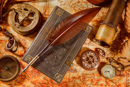antiquity: Vintage still life - magnifying glass, pocket watch, old book and goose quill pen lying on an old map in 1565.