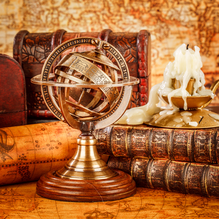 timekeeping: Vintage still life. Vintage old book and armillary sphere on an ancient world map in 1565.