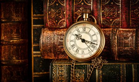 libros antiguos: Antiguo reloj de bolsillo de la vendimia en el fondo de libros antiguos Foto de archivo