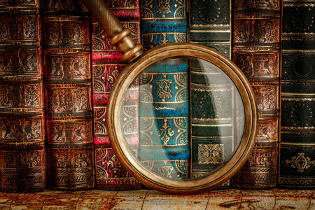 old books: Ancient old books and magnifying glass