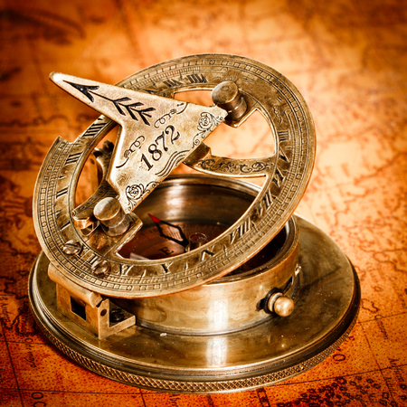 compass: Vintage still life. Vintage compass lies on an ancient world map in 1565. Stock Photo