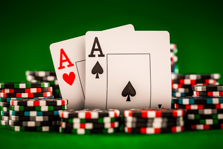 Stack van chips en twee azen op de tafel op het groene laken - poker game concept