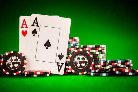 cartas de poker: Pila de fichas y dos ases en la tabla sobre el tapete verde - concepto de juego de póquer Foto de archivo