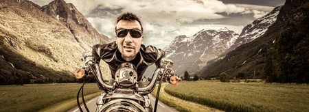 postproduction: Funny Biker in sunglasses and leather jacket racing on mountain serpentine. Filter applied in post-production. Stock Photo