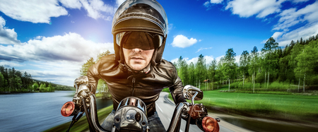 postproduction: Biker in helmet and leather jacket racing on the road. Filter applied in post-production.