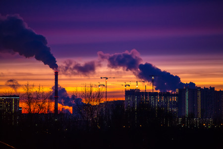 urbanization: Modern city in the evening at sunset. Smoke comes out of the pipes of power plants and factories of the modern neighborhood on the outskirts of the metropolis. Urbanization.