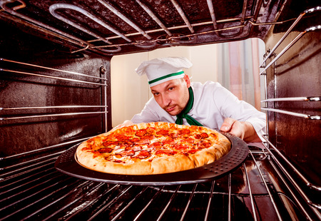 grates: Chef prepares pepperoni pizza in the oven, view from the inside of the oven. Cooking in the oven.