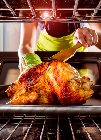 roasted turkey: Housewife prepares roast chicken in the oven, view from the inside of the oven. Cooking in the oven. Stock Photo
