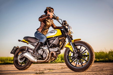 scrambler: RUSSIA-AUGUST 11, 2015:Biker girl on a Scrambler Icon Ducati. A new Scrambler was introduced at the 2014 Intermot motorcycle show.Ducati is an Italian company that designs and manufactures motorcycles Editorial