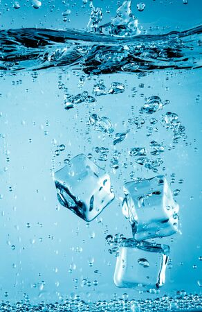 falling water: Ice cubes falling into the water sinking to the bottom. Abstract background.