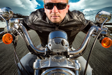 postproduction: Biker in sunglasses and leather jacket racing on mountain serpentine. Filter applied in post-production.