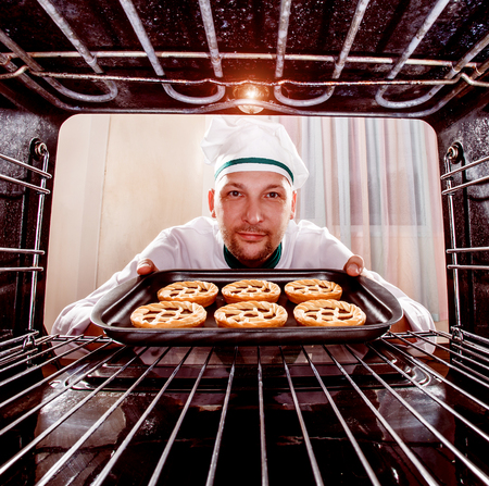 christmas baker's: Chef prepares pastries in the oven, view from the inside of the oven. Cooking in the oven. Stock Photo