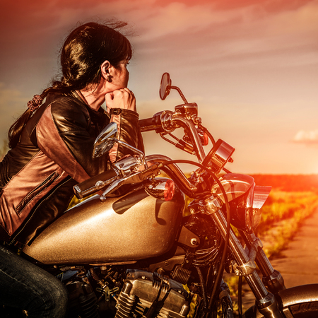 girl sitting: Biker girl in a leather jacket on a motorcycle looking at the sunset.