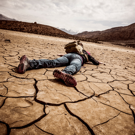 arid climate: traveller lays on the dried ground