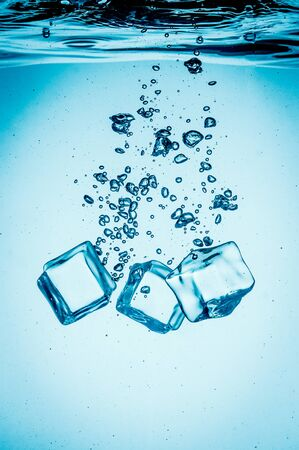 falling cubes: Ice cubes falling into the water sinking to the bottom. Abstract background.