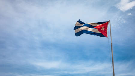 cuban flag: Cuban flag flying in the wind on a backdrop of blue sky. National symbol. Stock Photo