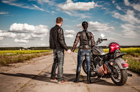 Biker man and girl stands on the road and looks into the distance Stock Photo
