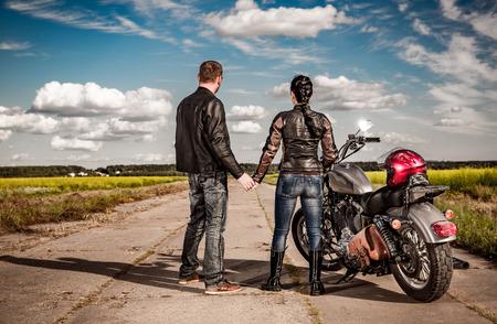 Biker man en meisje staat op de weg en kijkt in de verte Stockfoto
