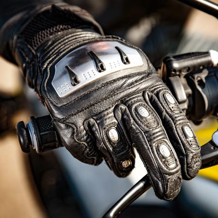 Menschlichen Hand in einem Motorrad Racing Handschuhe hält eine Motorrad-Drosselklappensteuerung. Handschutz bei Stürzen und Unfällen.