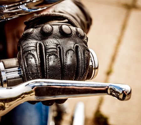 bike race: Human hand in a Motorcycle Racing Gloves holds a motorcycle throttle control. Hand protection from falls and accidents.