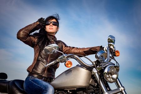 Biker meisje in een leren jack op een motorfiets te kijken naar de zonsondergang.