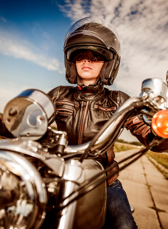motor bike: Biker girl in a leather jacket and helmet on a motorcycle