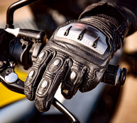 kevlar: Human hand in a Motorcycle Racing Gloves holds a motorcycle throttle control. Hand protection from falls and accidents.