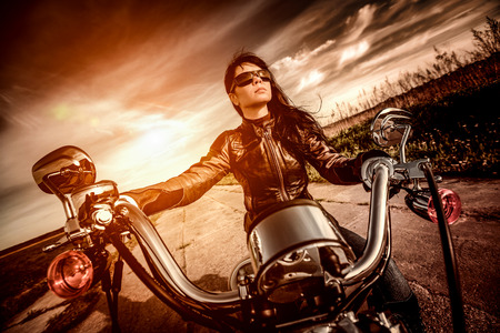postproduction: Biker girl in a leather jacket on a motorcycle looking at the sunset. Filter applied in post-production.