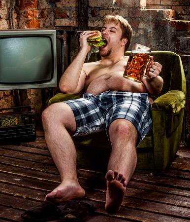 hombre sentado: hombre gordo comiendo hamburguesa sentado en la butaca