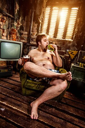 man eating: fat man eating hamburger seated on armchair