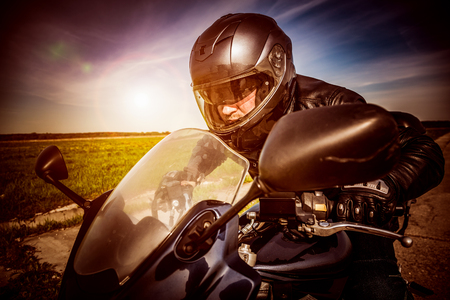 Biker in helmet and leather jacket racing on the road. Filter applied in post-production. photo