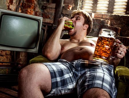beef burger: fat man eating hamburger seated on armchair