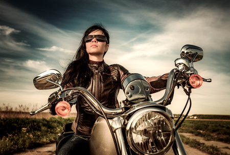 sexy girl posing: Biker girl with sunglasses sitting on motorcycle