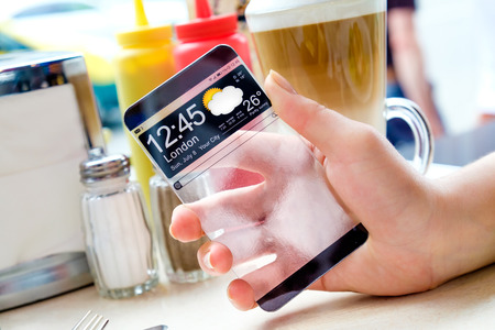 actual: Futuristic Smart phone with a transparent display in human hands. Concept actual future innovative ideas and best technologies humanity.