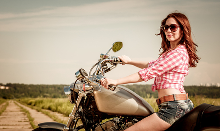 MOTORCYCLES: Biker girl with sunglasses sitting on motorcycle