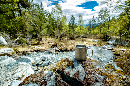 Travel titanium cup. Lunch during the journey to the wild. Camping lifestyle. Stock Photo