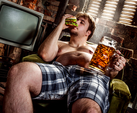 fat belly: fat man eating hamburger seated on armchair