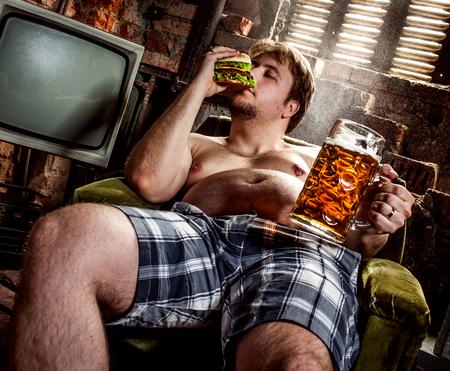 hombre tomando cerveza: hombre gordo comiendo hamburguesa sentado en la butaca