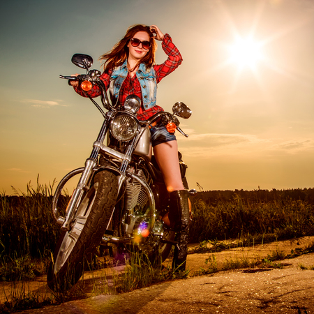 woman freedom: Biker girl with sunglasses sitting on motorcycle