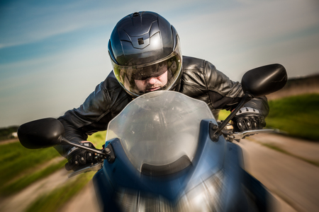 a helmet: Biker in helmet and leather jacket racing on the road Stock Photo