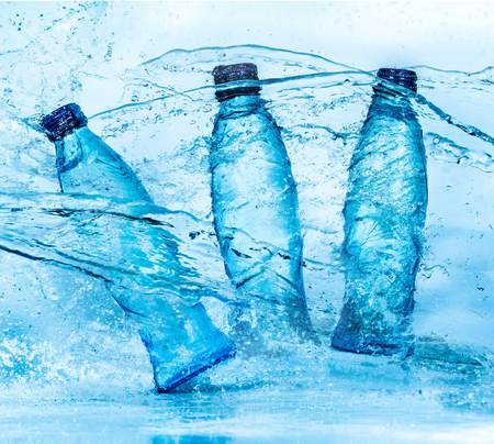 bottle with water: Bottle of water splash on a blue background Stock Photo