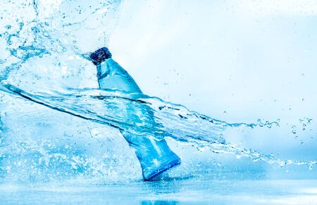 Mineral: Bottle of water splash on a blue background Stock Photo