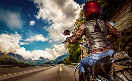 aventura: Muchacha del motorista monta una motocicleta en la lluvia. Vista en primera persona.