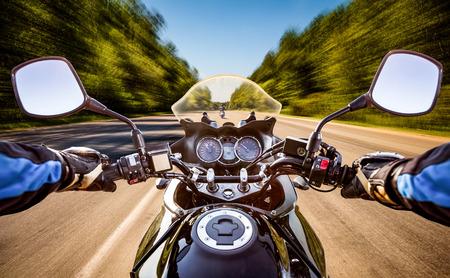 Fietser rijdt een motorfiets langs de asfaltweg. Eerste persoon bekijken.