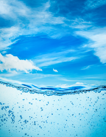 Many air bubbles in water close up, abstract water wave with bubbles on a background of blue sky Foto de archivo