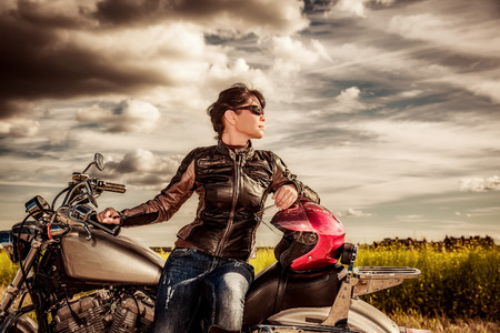 mooie vrouwen: Biker girl in a leather jacket on a motorcycle looking at the sunset.