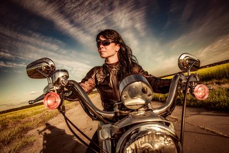 motorrad frau: Radfahrermädchen in einer Lederjacke auf einem Motorrad