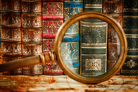 ancient books: Ancient old books and magnifying glass