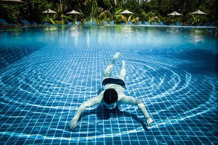 under: Man dives into a swimming pool views over the water and under water. Maldives. Stock Photo